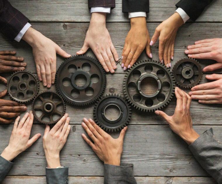 6 pairs of hands turning 6 interlocking cogs